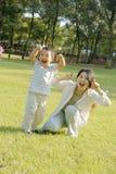 Junge und Mutter, die Gesichter auf Rasen bilden Stockfotos