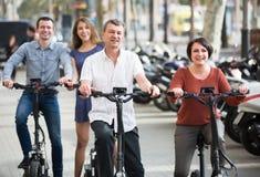 Junge und reife Paare, die mit den Fahrrädern im Freien bleiben Stockfoto