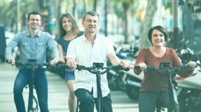 Junge und reife Paare, die mit den Fahrrädern im Freien bleiben Stockfotografie