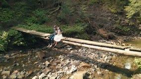 Junge und schöne Paare sitzen zusammen auf einer Brücke über dem kleinen Fluss im Park Sommerwetter Schießen von der Luft stock footage