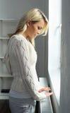 Junge und schöne blonde Frau, die den Heizkörper berührt Lizenzfreies Stockfoto