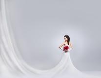 Junge und schöne Braut, die mit einem Blumenblumenstrauß steht Stockbild