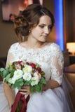 Junge und schöne Braut mit Blumenblumenstrauß im Hotel Stockfotografie