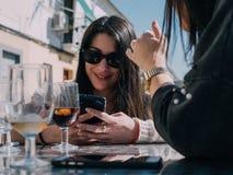Junge und schöne Freunde, die ein Auffrischungsgetränk auf einer Terrasse einer Tagesbar haben lizenzfreie stockfotos