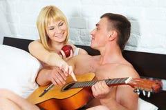 Junge und schöne Paare im Bett Lizenzfreie Stockfotos
