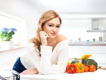 Junge und schöne Hausfraufrau, die in einer Küche kocht Stockbilder