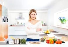 Junge und schöne Hausfraufrau, die in einer Küche kocht Stockfoto