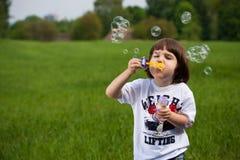Junge und Seifeluftblasen Stockfotos