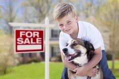 Junge und sein Hund vor für Verkaufs-Zeichen und Haus Lizenzfreie Stockfotos