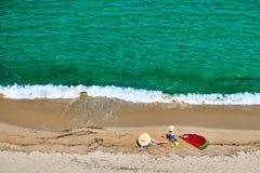 Junge und seine Mutter auf Strand mit aufblasbarem Floss lizenzfreies stockfoto