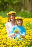 Junge und seine Mutter, die auf einem Löwenzahn-Gebiet sitzen Lizenzfreie Stockbilder