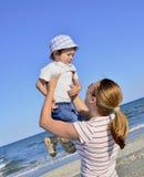 Junge und seine Mutter am Strand Stockbild