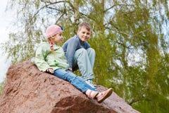 Junge und seine Schwester sitzen auf großem Block des roten Granits Lizenzfreie Stockfotos