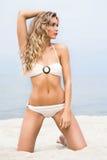 Junge und sexy blonde Frau, die auf dem Strand aufwirft Lizenzfreie Stockfotografie