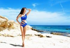 Junge und sexy Frau, die in einem blauen Badeanzug auf dem Strand aufwirft Lizenzfreie Stockfotos