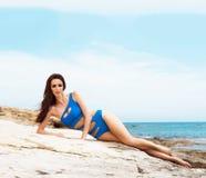 Junge und sexy Frau, die in einem blauen Badeanzug auf dem Strand aufwirft Stockfotos