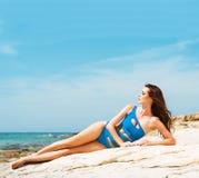 Junge und sexy Frau, die in einem blauen Badeanzug auf dem Strand aufwirft Lizenzfreies Stockbild