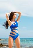 Junge und sexy Frau, die in einem blauen Badeanzug auf dem Strand aufwirft Lizenzfreies Stockfoto