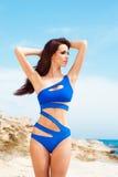 Junge und sexy Frau, die in einem blauen Badeanzug auf dem Strand aufwirft Lizenzfreie Stockfotografie