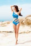 Junge und sexy Frau, die in einem blauen Badeanzug auf dem Strand aufwirft Lizenzfreie Stockbilder