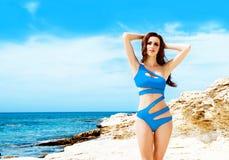 Junge und sexy Frau, die in einem blauen Badeanzug auf dem Strand aufwirft Stockfotografie