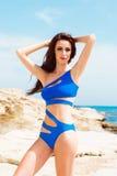 Junge und sexy Frau, die in einem blauen Badeanzug auf dem Strand aufwirft Stockbilder