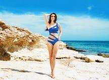 Junge und sexy Frau, die in einem blauen Badeanzug auf dem Strand aufwirft Stockfoto