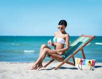 Junge und sexy Frau, die Sonnencreme auf dem Strand verwendet Lizenzfreie Stockfotos