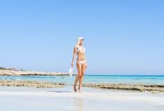 Junge und sexy Frau in einem Bikini auf dem Strand Lizenzfreie Stockbilder