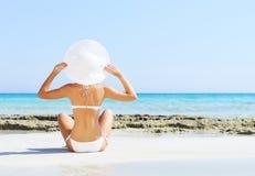 Junge und sexy Frau in einem Bikini auf dem Strand Lizenzfreie Stockfotos