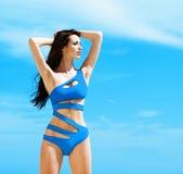 Junge und sexy Frau in einem blauen Badeanzug auf dem Strand Stockbild