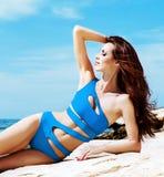 Junge und sexy Frau in einem blauen Badeanzug auf dem Strand Lizenzfreie Stockfotos