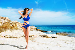 Junge und sexy Frau in einem blauen Badeanzug auf dem Strand Lizenzfreies Stockfoto