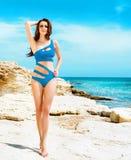 Junge und sexy Frau in einem blauen Badeanzug auf dem Strand Lizenzfreies Stockbild