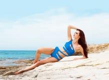 Junge und sexy Frau in einem blauen Badeanzug auf dem Strand Stockbilder