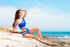 Junge und sexy Frau in einem blauen Badeanzug auf dem Strand Lizenzfreie Stockbilder