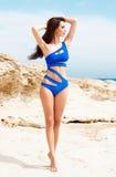 Junge und sexy Frau in einem blauen Badeanzug auf dem Strand Stockfotografie