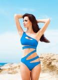 Junge und sexy Frau in einem blauen Badeanzug auf dem Strand Lizenzfreie Stockfotografie