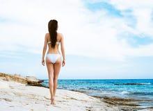 Junge und sexy Frau in einem weißen Badeanzug auf dem Strand Lizenzfreie Stockbilder