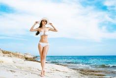 Junge und sexy Frau in einem weißen Badeanzug auf dem Strand Stockfoto
