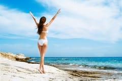 Junge und sexy Frau in einem weißen Badeanzug auf dem Strand Stockbild