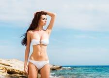 Junge und sexy Frau in einem weißen Badeanzug auf dem Strand Lizenzfreie Stockfotografie