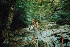 Junge und sexy Frau sitzen auf tragendem Badeanzug des Felsens auf dem schönen Wasserfall im Dschungel stockfotos
