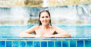 Junge und sportliche Frau im Badeanzug Mädchen, das in einem Pool am Sommer sich entspannt stockfotos