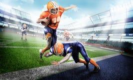 Junge und starke Spieler des amerikanischen Fußballs auf grünem Gras Lizenzfreies Stockfoto