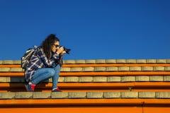 Junge und stilvolle Frau mit der Kamera, die auf der Bank sitzt Stockfotografie