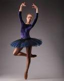 Junge und unglaublich schöne Ballerina in der blauen Ausstattung ist, tanzend aufwerfend und in Studio Kunst des klassischen Ball Stockfoto