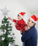Junge und Vater Decorating Christmas Tree Stockfotos