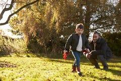 Junge und Vater Playing With Autumn Leaves im Garten Stockfotografie