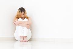 Junge unglückliche Frau sitzt auf dem Boden Der Raum ist leeres a Stockfotografie